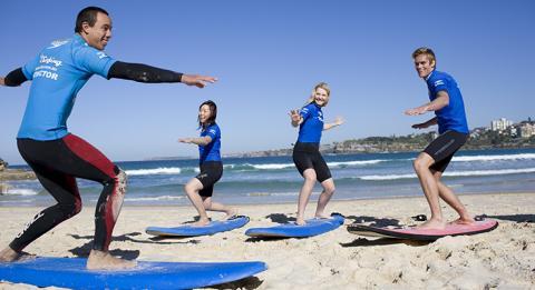 """Zwei junge Frauen und ein junger Mann lernen bei einem """"Let's Go Surfing""""-Lehrer am Bondi Beach Surfen"""