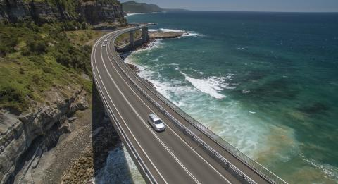 A car driving across the Sea Cliff Bridge, near Clifton