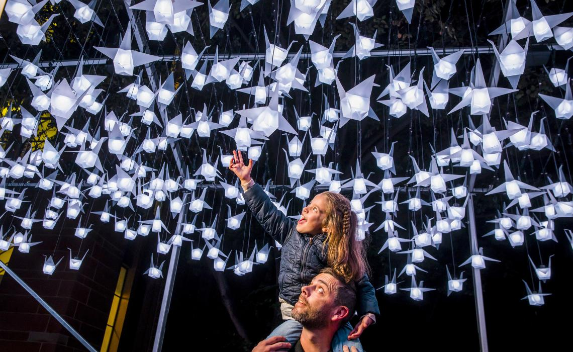 Family enjoying a close-up view of the 1000 Cranes light installation at First Fleet Park, The Rocks during Vivid Sydney 2018