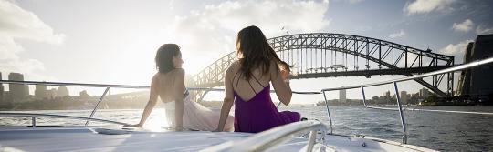 Zwei Frauen vor einer Yacht, die durch den Sydney Harbour segelt.